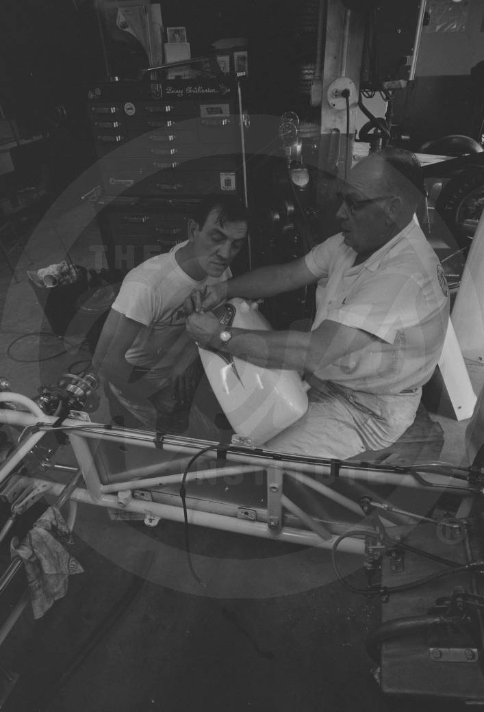 Crew members working on a car in the garage.