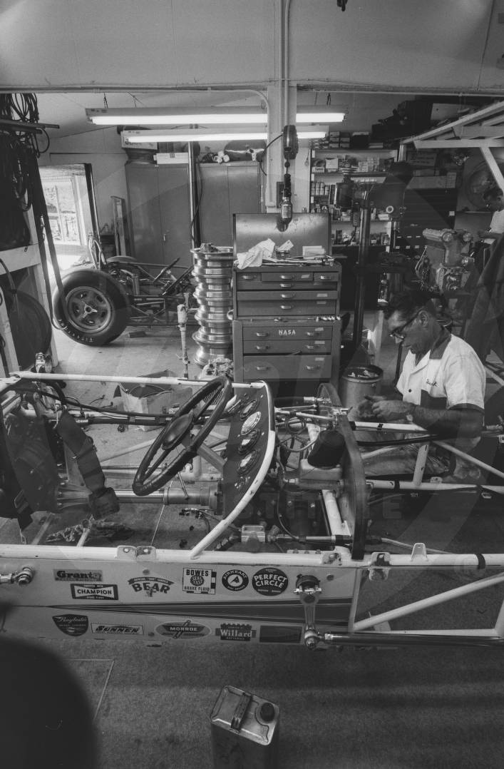 Crew member working on a car in the garage.