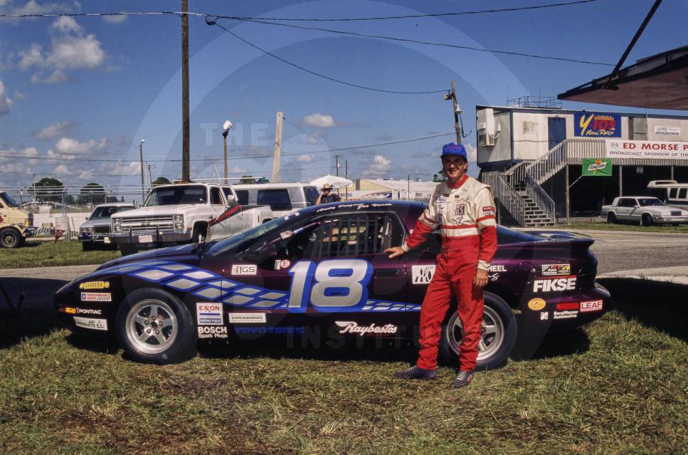 Andy Pilgrim poses next to car number 18, a Pontiac Firebird.